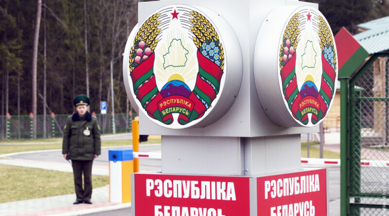 "Belarussian border guard stands near a pole with the state emblem, reading, ""Republic of Belarus"" at a border crossing with Poland near the village of Pererov"